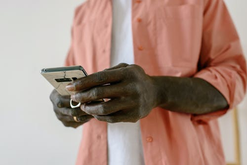 Person in Pink Dress Shirt Holding Silver Iphone 6