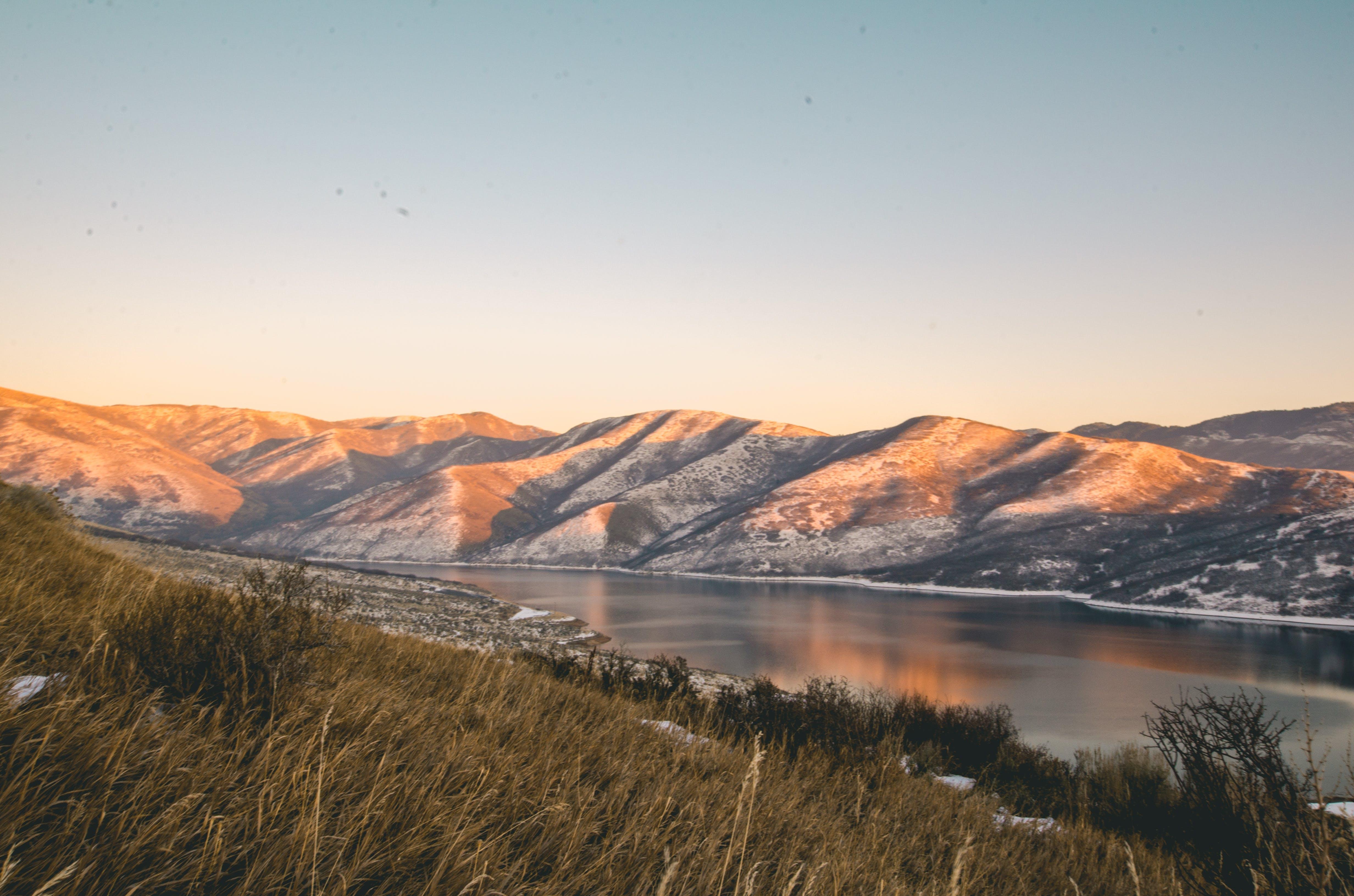 Mountains Near Lake Under Blue Sky