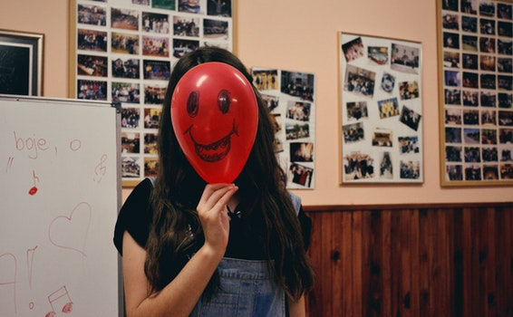 Woman Holding Red Balloon on Her Face Photo Inside Classroom