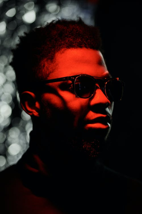 A Man Wearing Shades with a Red Light