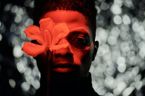 A Man Covering His Eye with a Flower