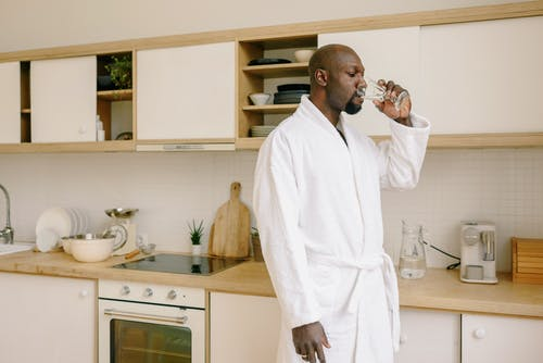 Man in White Robe Drinking from Clear Drinking Glass