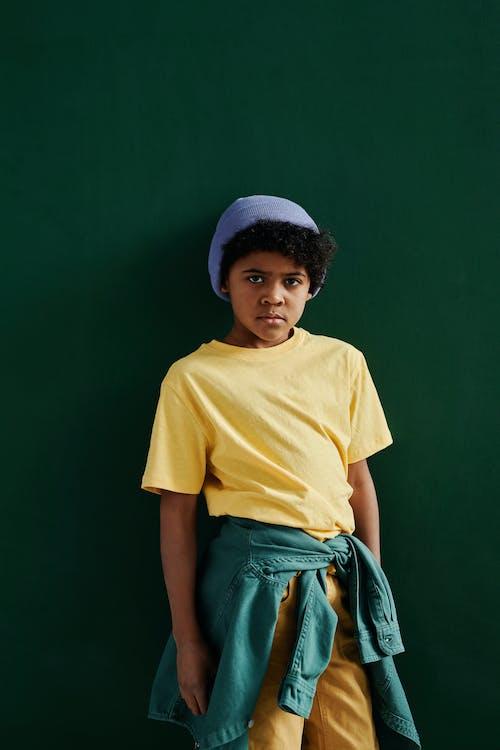 Boy in Yellow Crew Neck Shirt Standing Beside Green Wall