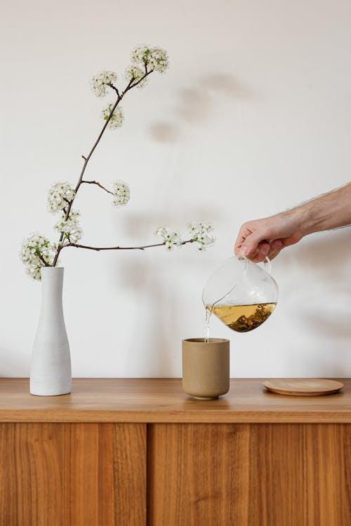A Person Pouring Tea into a Ceramic Cup