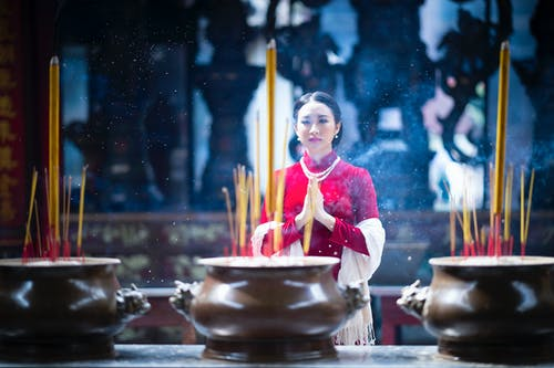 Calm young Asian woman with dark hair in elegant red dress praying with clasped hands while standing near copper pots with burning incense sticks in Buddhist temple