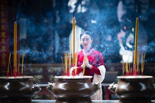Elegant young Asian woman praying in shrine near burning incense sticks