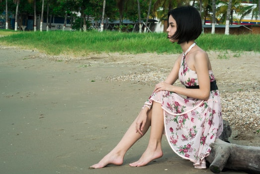 Woman in Pink Floral Halter Dress Seating in Driftwood