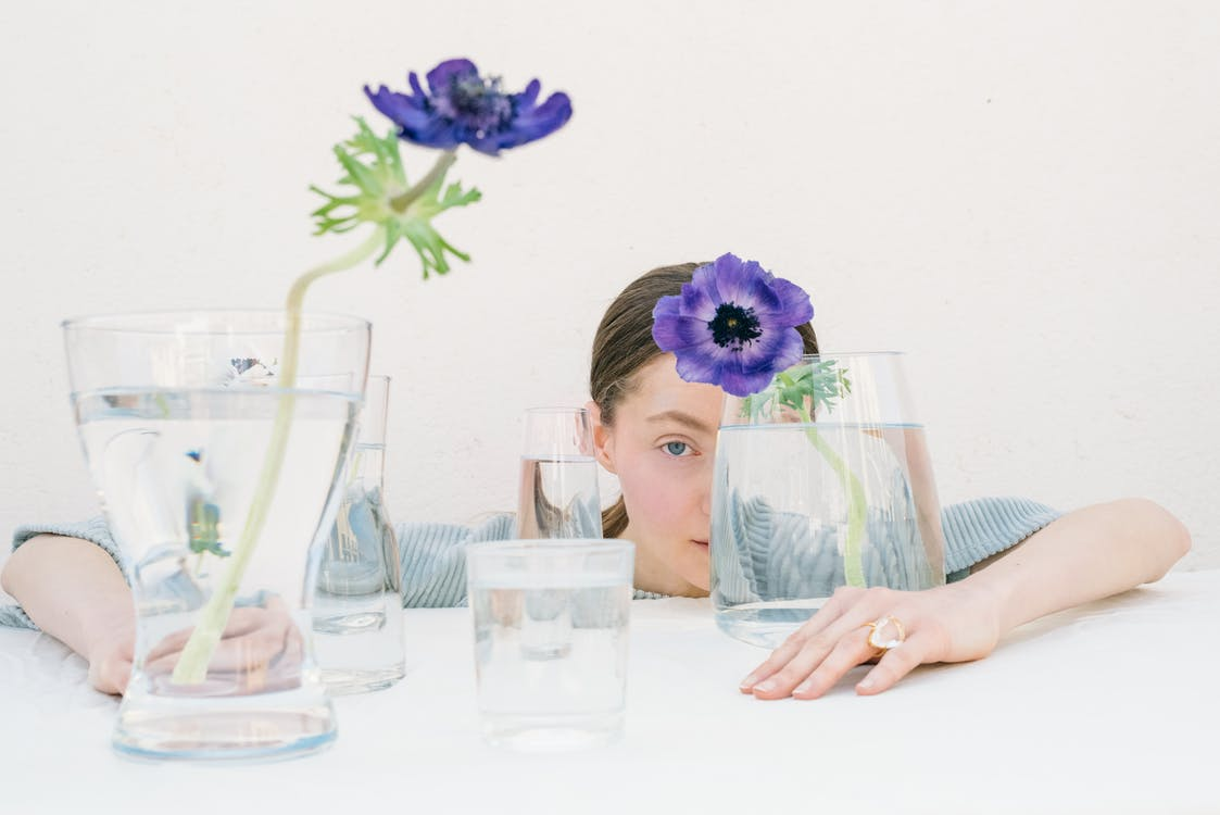 Woman in White Shirt Sitting Beside Table With Purple Flower