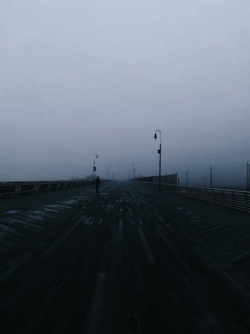 Anonymous person walking along asphalt road under gloomy sky