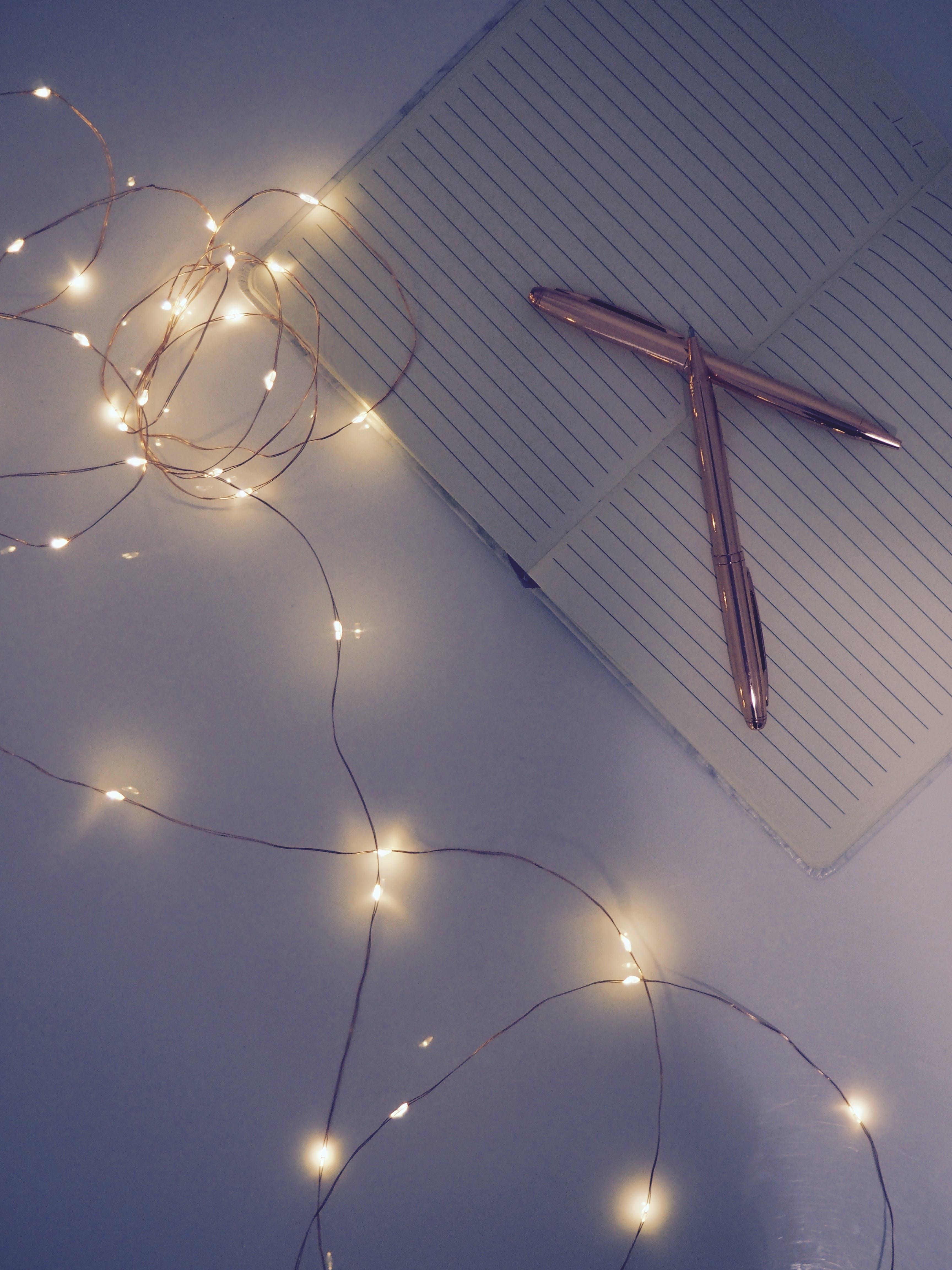 Darmowe zdjęcie z galerii z długopisy, lampki, notatnik, oświetlony