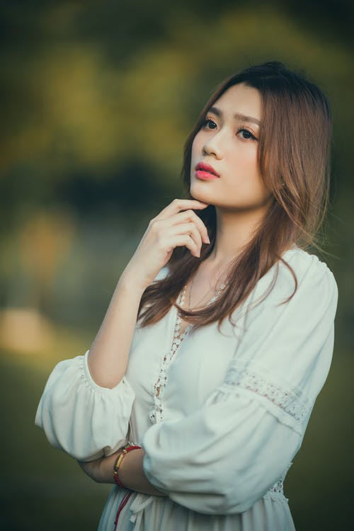 Thoughtful young elegant Asian lady touching chin and looking away in nature