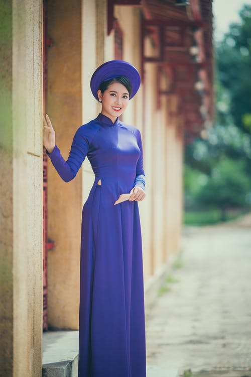 Positive Asian woman in stylish outfit standing near building in daytime