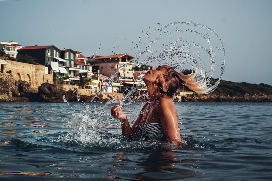 Time lapse photography of woman playing on water with her hair