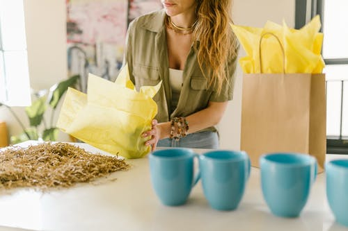 A Woman Wrapping a Mug with a Yellow Paper