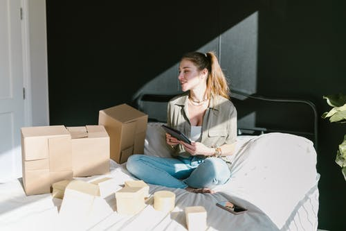 A Woman in Bed with Brown Boxes while Holding a Tablet