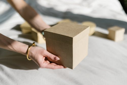 Person Holding Brown Box With Gold Ring