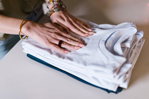 Person Wearing Silver Ring Holding White Crew Neck Shirt