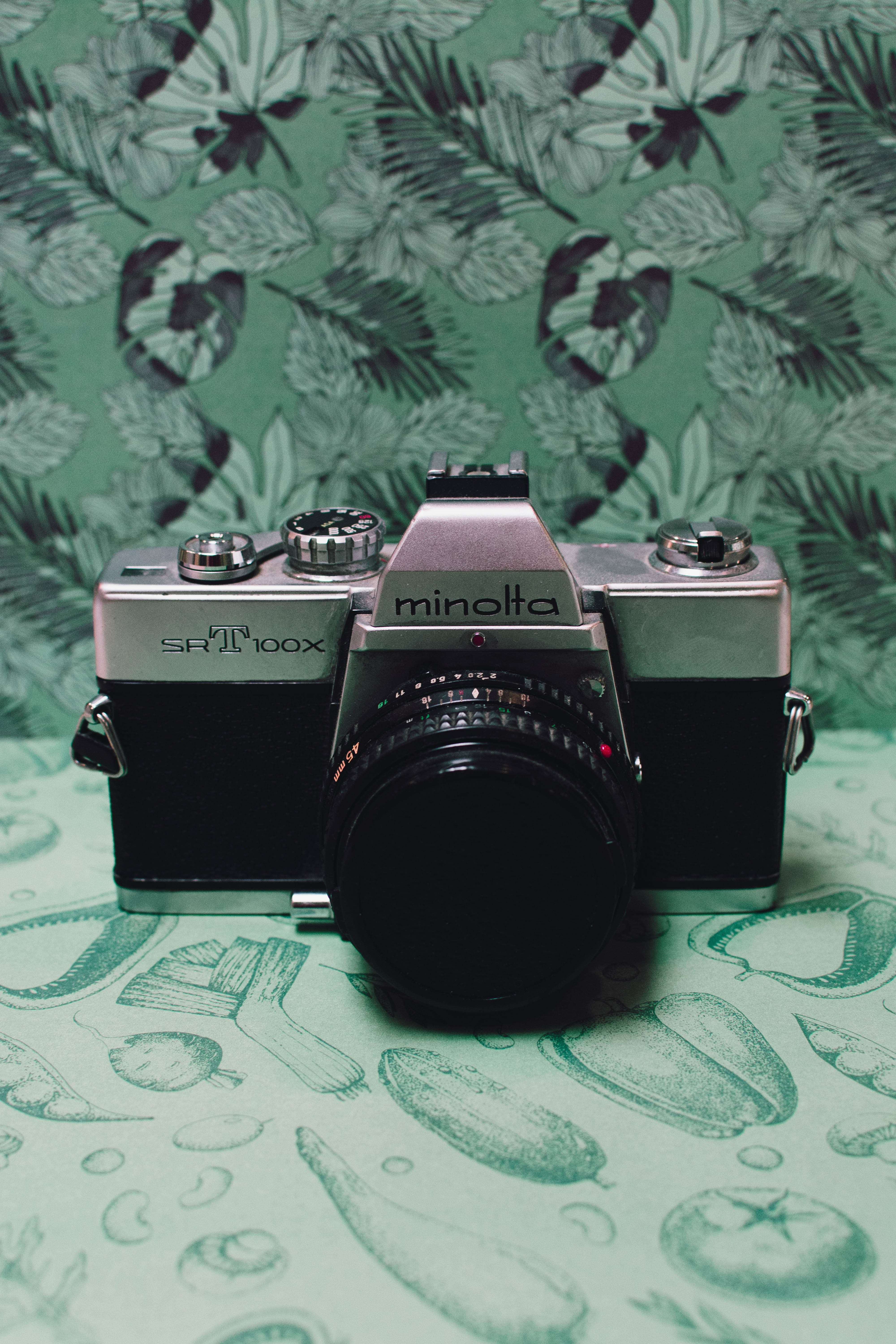 Black and Gray Film Camera on Green Floral Textile
