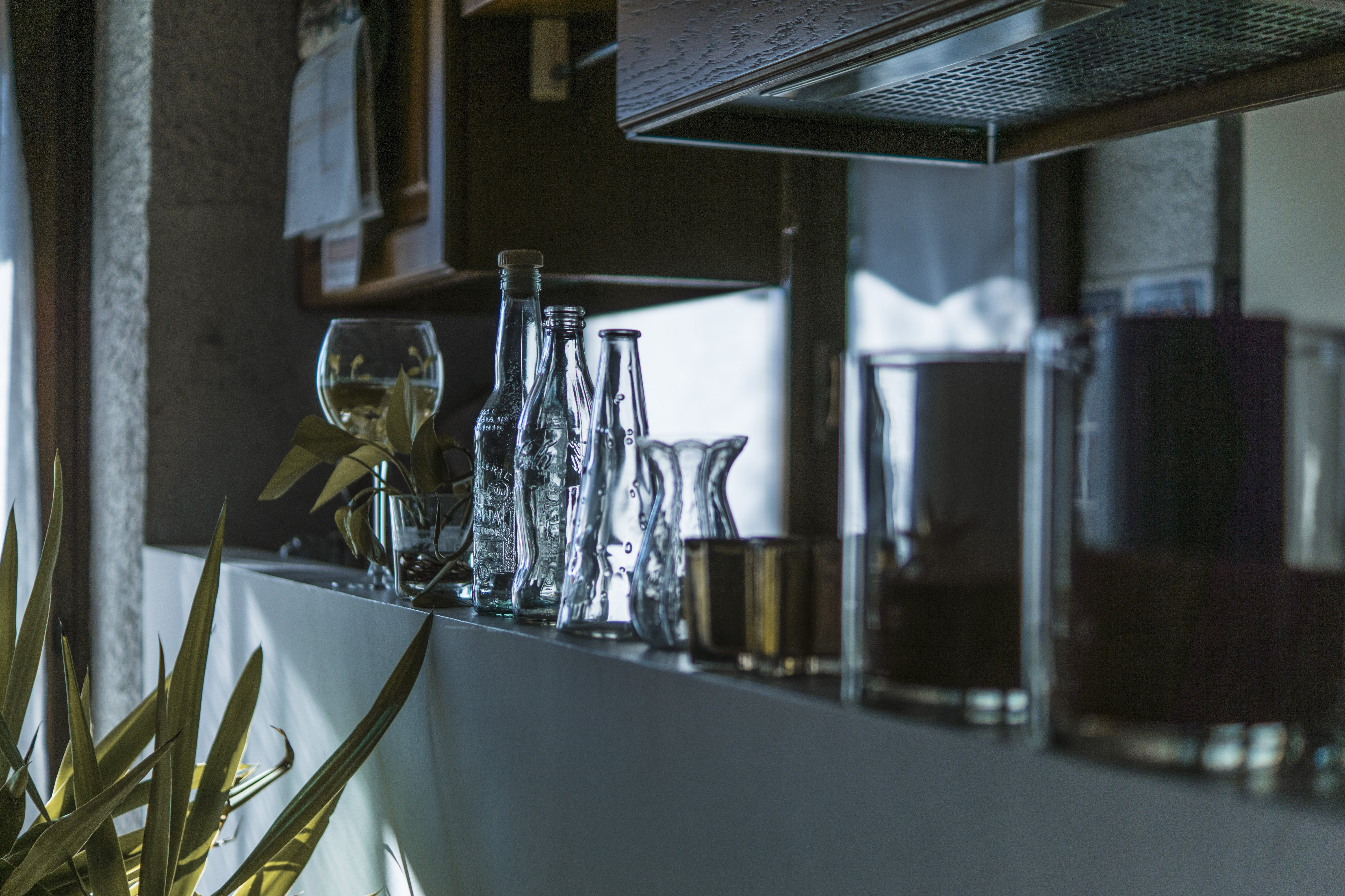 Assorted Clear Glass Bottles With Wine Glass in the Shelf