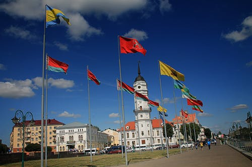 Different Flags Waving on Poles at Daytime