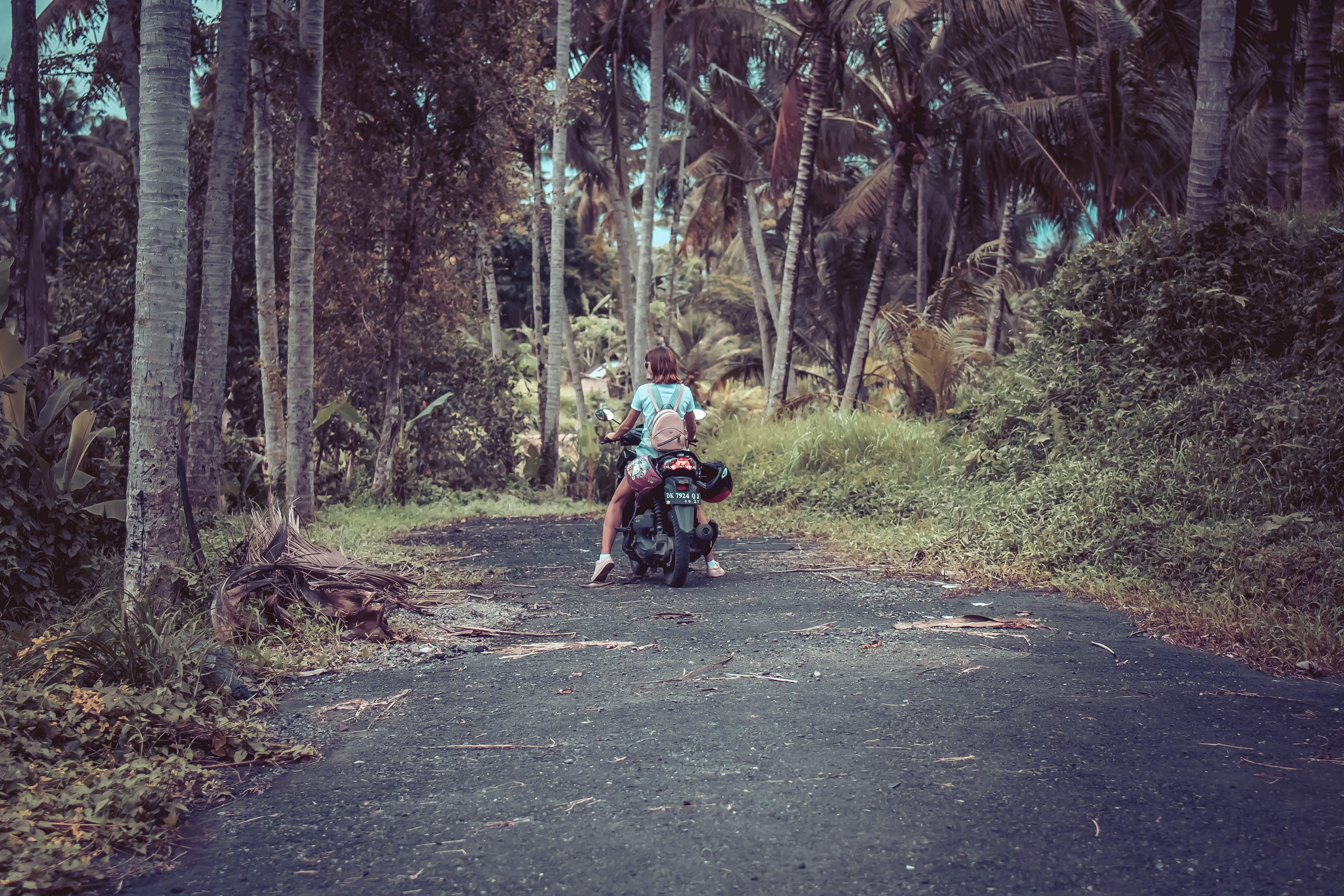Woman Riding Motor Scooter Near Coconut Trees