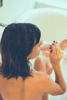 Woman on Bathtub Holding Clear Champagne Glass