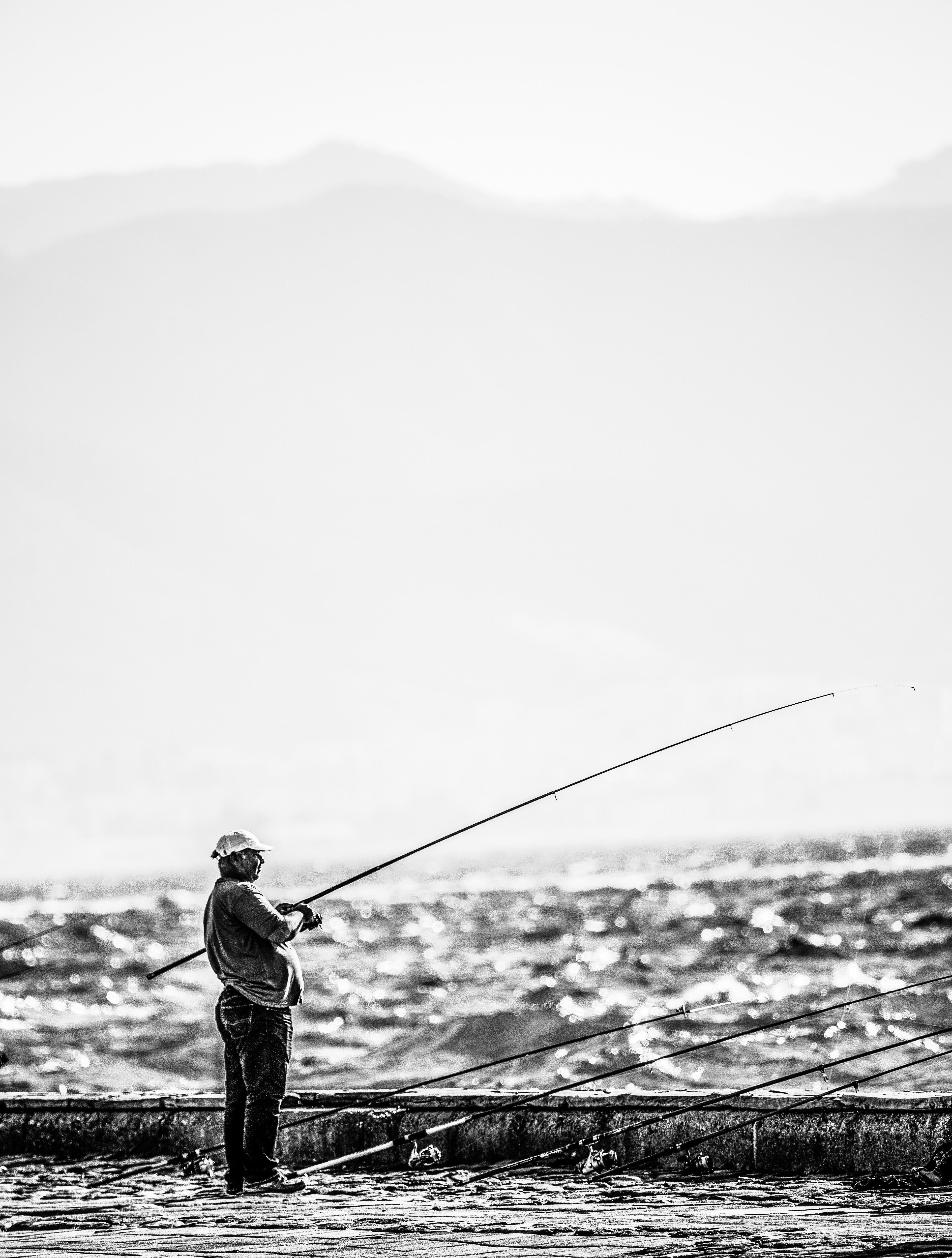 Man Standing Near Seashore Holding Fishing Rod on Grayscale Photography