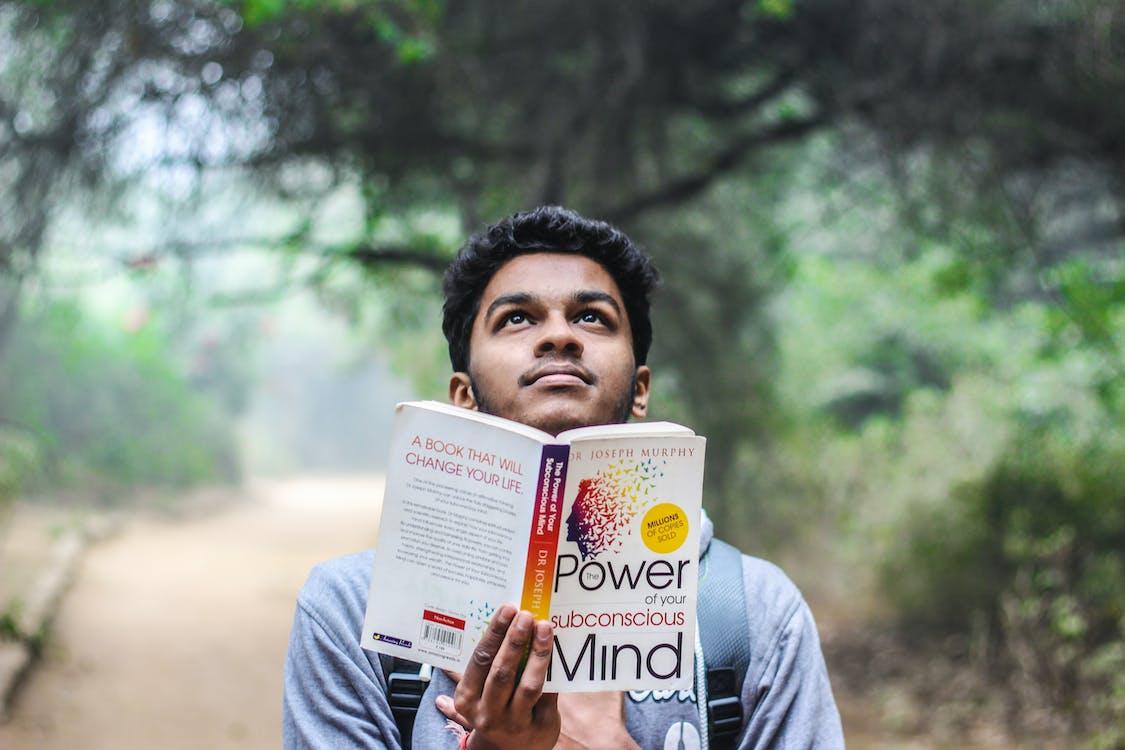 Man in Grey Shirt Holding Opened Book Looking Upward