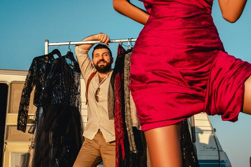 Cheerful man standing near rack with collection of fashionable garments on street with faceless woman and trailer while preparing for video shoot