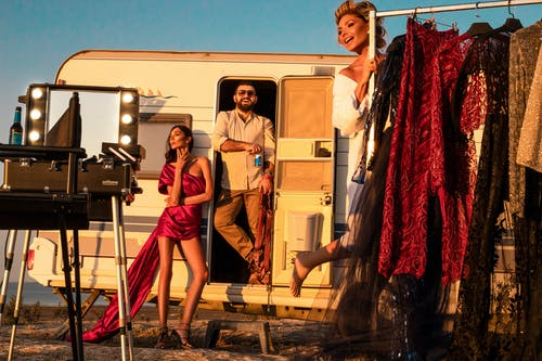 Full body of cheerful male standing in trailer near gorgeous women wearing stylish dresses on street with collection of outfits on rack and professional supply while preparing for video shoot