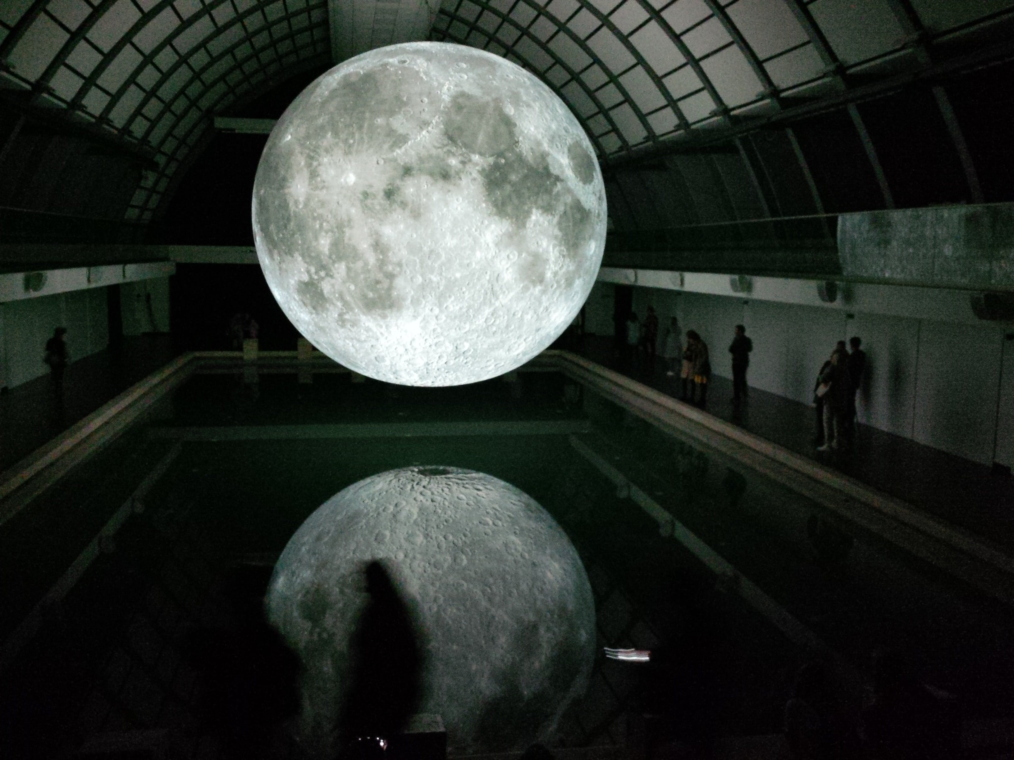 Photo of Moon Hologram Floating on Water Near People Inside Room