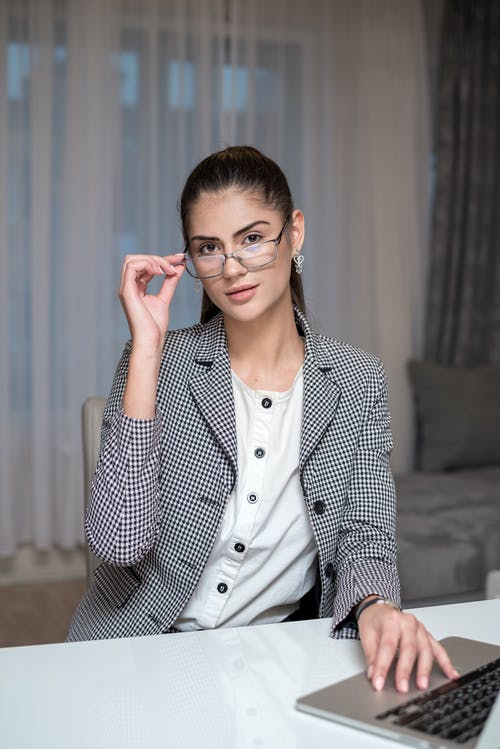 Woman in Black and White Pinstripe Blazer Sitting on Chair