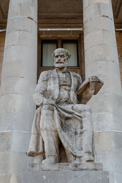 Stone Statue Of Man Holding A Book