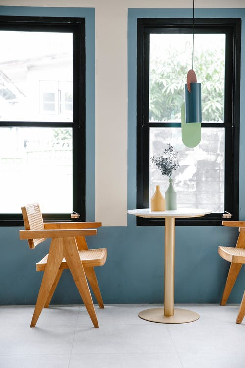 Geometric decoration hanging over table with blooming flowers in vase between armchairs against windows in daytime