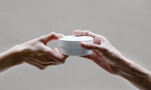 Crop woman passing jar of cream to girlfriend
