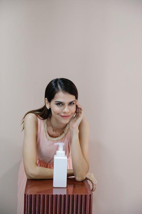 Smiling woman against sanitizer bottle on light background