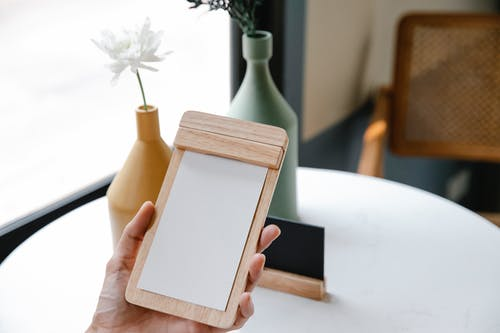 Crop unrecognizable person demonstrating blank notepad with wooden frame against blossoming flowers in vases on blurred background