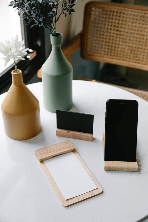 From above of wooden jotter with white sheets placed on round table near smartphone with black screen and visit card and composed with elegant vases with fresh flowers