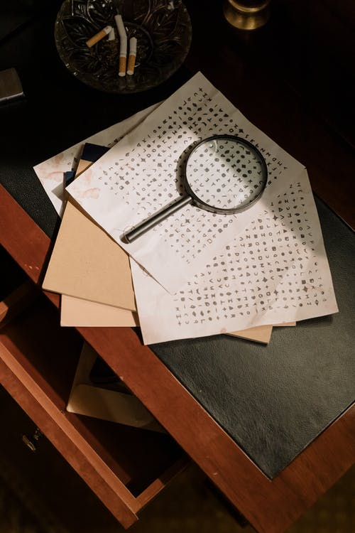 Photo of Cryptic Character Codes and Magnifying Glass on Table Top