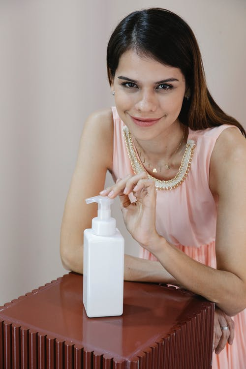 Smiling young woman showing bottle of cosmetic product