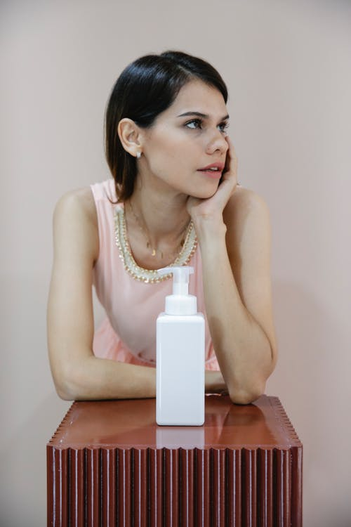 Thoughtful young lady with long dark hair leaning on hand on table with lotion white bottle with pump and looking away