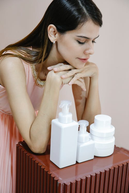 Pensive young woman leaning on table with bottles of assorted cosmetic products