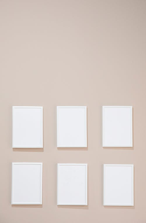Empty white photo frames hanging on gray wall