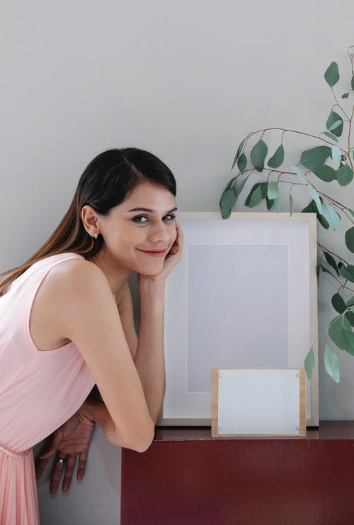 Side view of positive young female with long dark hair leaning on shelf with hand on cheek and smiling near frame mockup and vase with green leaves