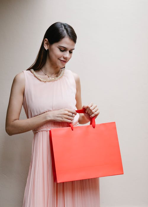 Self assured young elegant lady with long dark hair in stylish pink dress smiling while standing near white wall with red shopping bag in hand