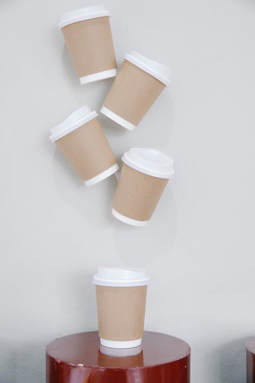 Collection of similar cups of takeaway coffee with kraft papers placed on small round table and hanging on white wall