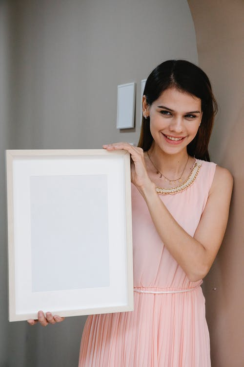 Graceful lady demonstrating frame mockup and smiling at camera