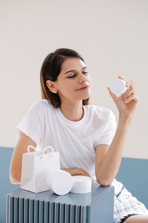 Confident young woman showing white jars of creams in studio