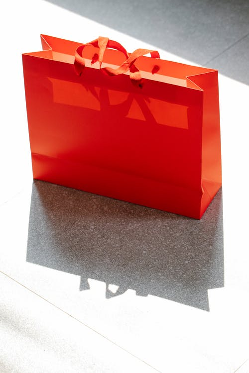 Red shopping bag placed on street in daylight