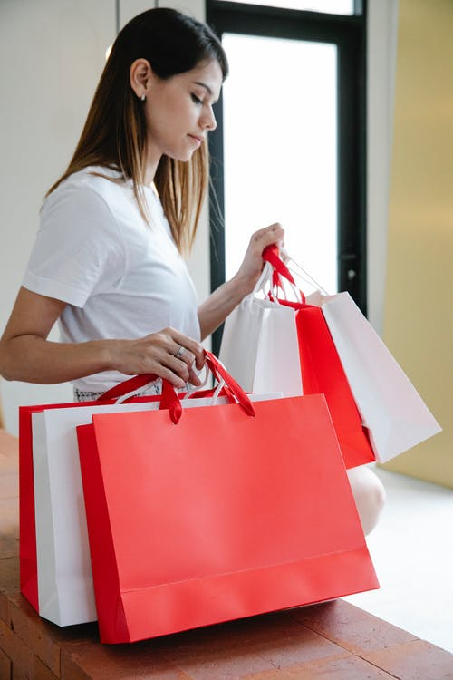 Side view of stylish young female millennial with long dark hair in t shirt sitting on bricj bench with white and red paper bags after shopping